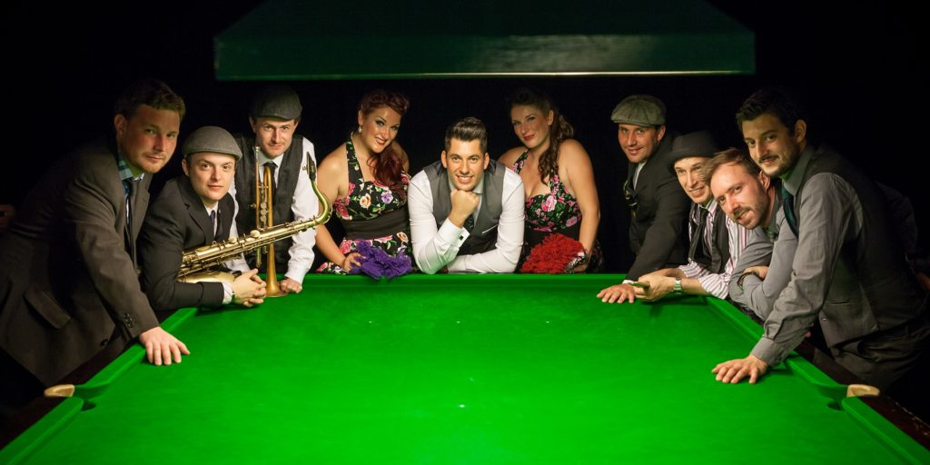 Phil Lyons and the New Vintage band in front of pool table